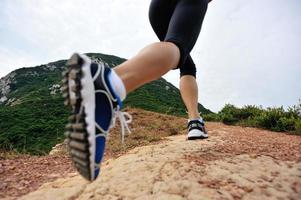 gambe di giovane donna asiatica in esecuzione sul sentiero di montagna al mare foto