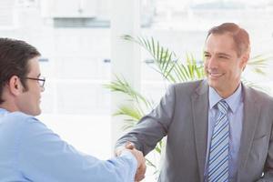 uomo d'affari sorridente che agita le mani con un collega foto