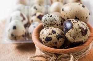 uova di quaglia crude in una ciotola di legno su sfondo di tela foto