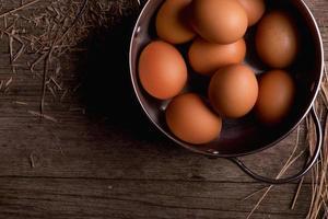 uova di gallina in padella su fondo di legno rustico foto