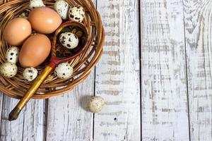 uova di gallina e quaglia con un cucchiaio di legno foto