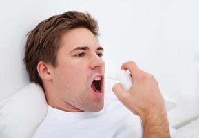 uomo che per mezzo dell'inalatore di asma foto