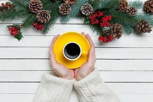 ragazza che tiene tazza di caffè vicino ai rami di pino foto