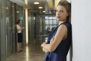donna di affari che si appoggia in corridoio dell'ufficio foto