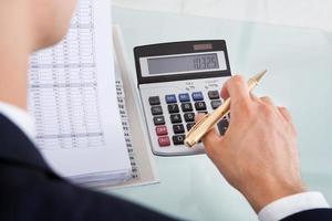 spesa calcolatrice della tenuta dell'uomo d'affari in ufficio