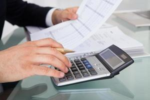 spesa calcolatrice della tenuta dell'uomo d'affari in ufficio foto