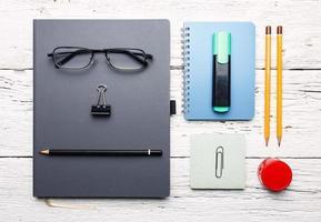 posto di lavoro. tavolo in legno bianco con blocco note, matite colorate e foto