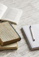 pila di libri, taccuino sulla tavola di legno bianca. foto