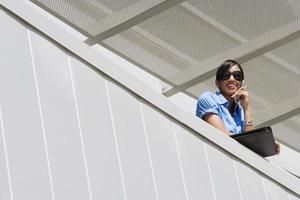 felice imprenditrice su chiamata in ufficio balcone foto