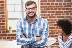 uomo d'affari sorridenti con le braccia incrociate in ufficio foto