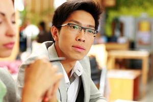 riflessivo uomo asiatico con gli occhiali in ufficio foto