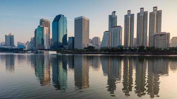 edificio per uffici di Bangkok con la riflessione dell'acqua durante l'alba foto
