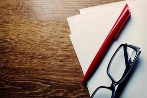 penna e occhiali da lettura su carta bianca foto