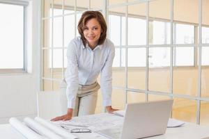 fiduciosa giovane imprenditrice sorridente in ufficio foto