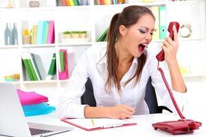 donna di affari arrabbiata con il telefono all'ufficio foto