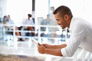 Ritratto di uomo in ufficio utilizzando la tavoletta, sorridente foto