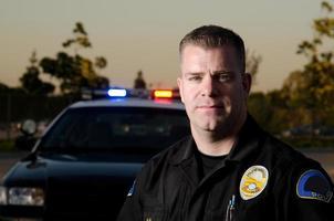colpo di testa di sera del poliziotto maschio con auto dietro foto