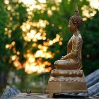 scultura dorata della statua di Buddha con il fondo della luce del bokeh foto