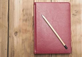 taccuino di cuoio rosso con la matita su fondo di legno foto