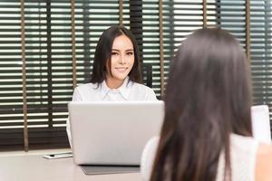 due donne d'affari che lavorano in ufficio su un computer portatile foto