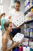 donna che seleziona la carta igienica nel deposito foto
