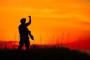 sagoma del soldato militare o ufficiale con armi al tramonto foto