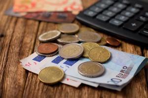 pila di banconote e monete in euro più due carte di credito foto