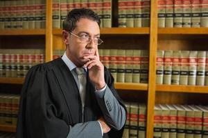 avvocato che pensa nella biblioteca di legge