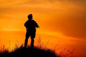 sagoma del soldato militare o ufficiale con armi al tramonto