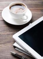 tablet, taccuino di carta e caffè sul tavolo foto