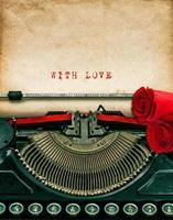 macchina da scrivere vintage e fiori di rose rosse. Con amore