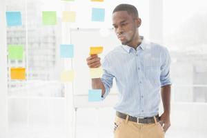 uomo d'affari casuale che legge le note appiccicose sulla finestra foto