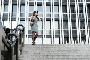 elegante giovane imprenditrice parlando per telefono in strada foto