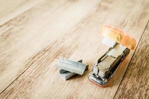 carta della cucitrice meccanica su fondo di legno foto