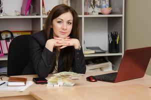 donna d'affari alla scrivania con una pila di soldi foto