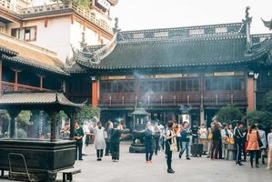 adoratori e turisti nel tempio buddista di shanghai foto