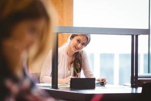 studente sorridente seduto accanto alla finestra prendendo appunti foto