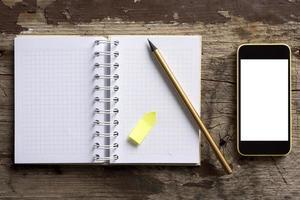 telefono e blocco note sul tavolo di legno foto