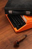 macchina da scrivere vintage arancione sul legno foto