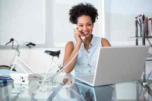 giovane donna casuale che per mezzo del telefono e del computer portatile foto