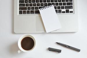 tazza di caffè, blocco note a spirale, tastiera del computer e penna su bianco