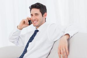 uomo d'affari che chiama con il suo telefono cellulare sul divano foto