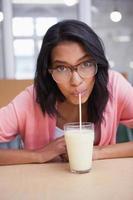 donna che beve un bicchiere di latte mentre guarda la telecamera foto