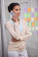 donna dai capelli castani che chiama con il suo telefono cellulare foto