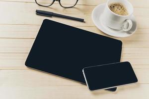 telefono cellulare e tablet con notebook sulla scrivania