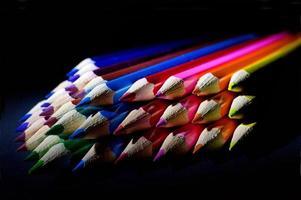 colpo a macroistruzione di matite colorate affilate su sfondo nero