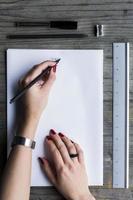 scrittura della mano della donna sul Libro Bianco foto