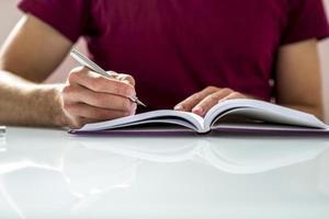 primo piano di uno studente scrivere appunti o compiti a casa foto