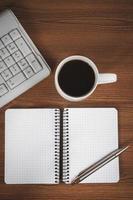 blocco note vuoto, tastiera, penna e tazza di caffè foto