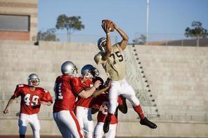 avversari giocatori di football americano in competizione per la palla foto